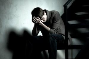 Depressed man sitting on steps in dark corridor