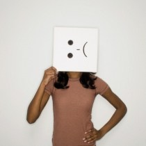 Woman holding sad face sign