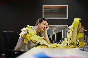 Businessman at desk covered with sticky notes