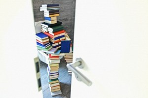 Figure made of books sitting on a toilet
