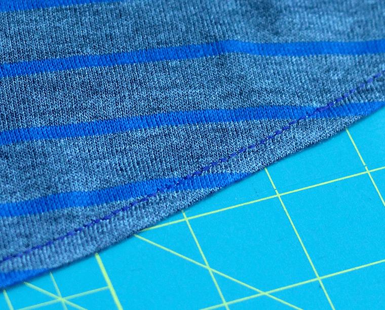 Topstitch knit fabric with a three-part straight stitch or narrow zig-zag.