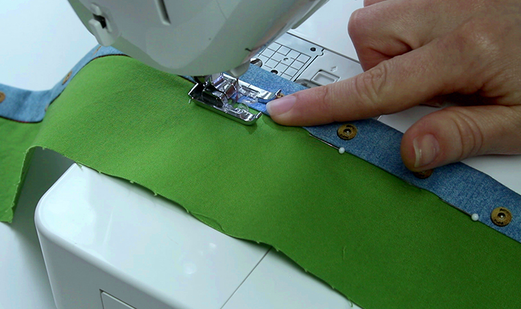 Stitch in the ditch on the front, catching the seam allowance fold on the inside of the pants/skirt.