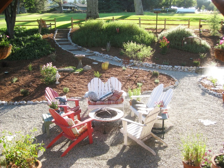 A Gravel Patio Features Adirondack Chairs And A Fire Pit Sierra