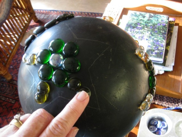 I placed the ball on a pedestal. You could also use a folded towel. After drawing the shape on the ball four times, one on each side, I started gluing the gem's on.