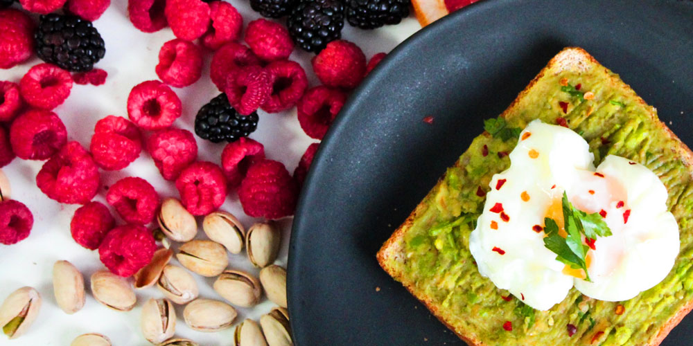 Healthy toast with egg, next to nuts and berries