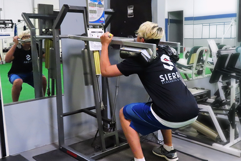 Person squats down using weighted squat machine