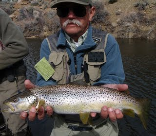 Large Brown held up by an Man in a Mustache on the bank of the RIver
