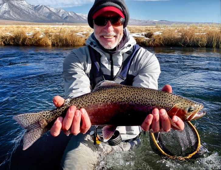 Man holds a large brightly striped Rainbow Trout over the water