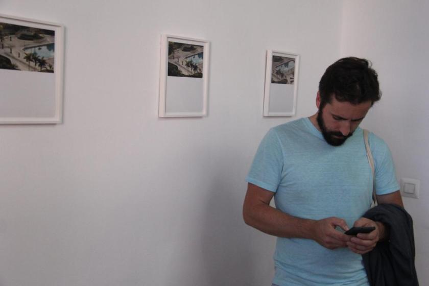 Un joven chequea su móvil ante algunas de las fotografías expuestas en fluent