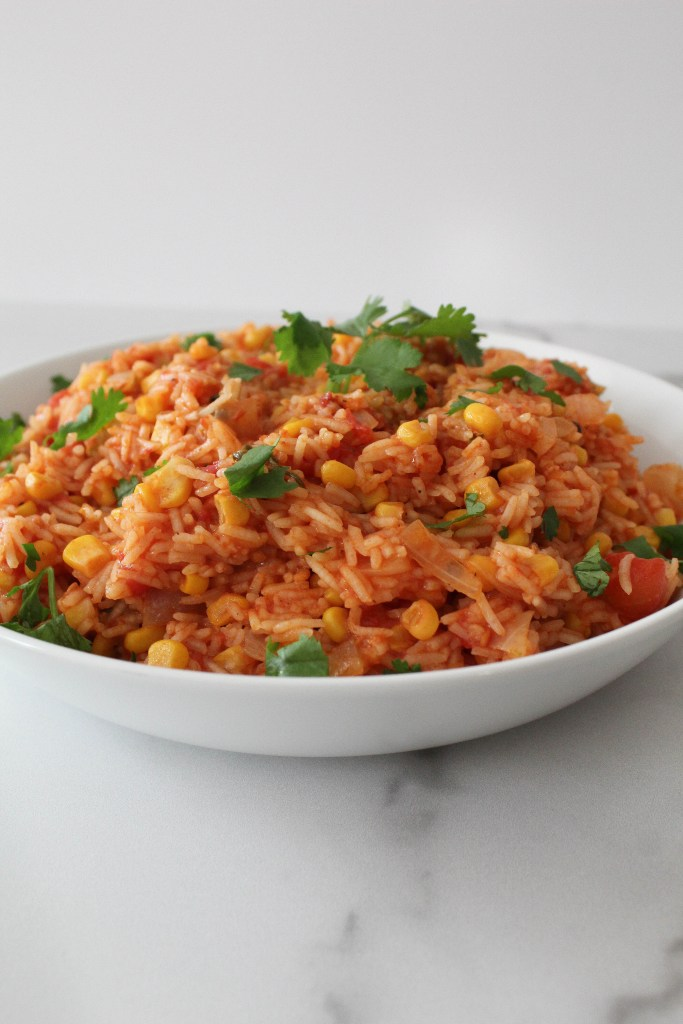 Rice braised in a tomato sauce in a white bowl with vegetables and cilantro.