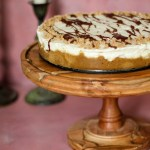 heath bar cheesecake on a wooden cake stand