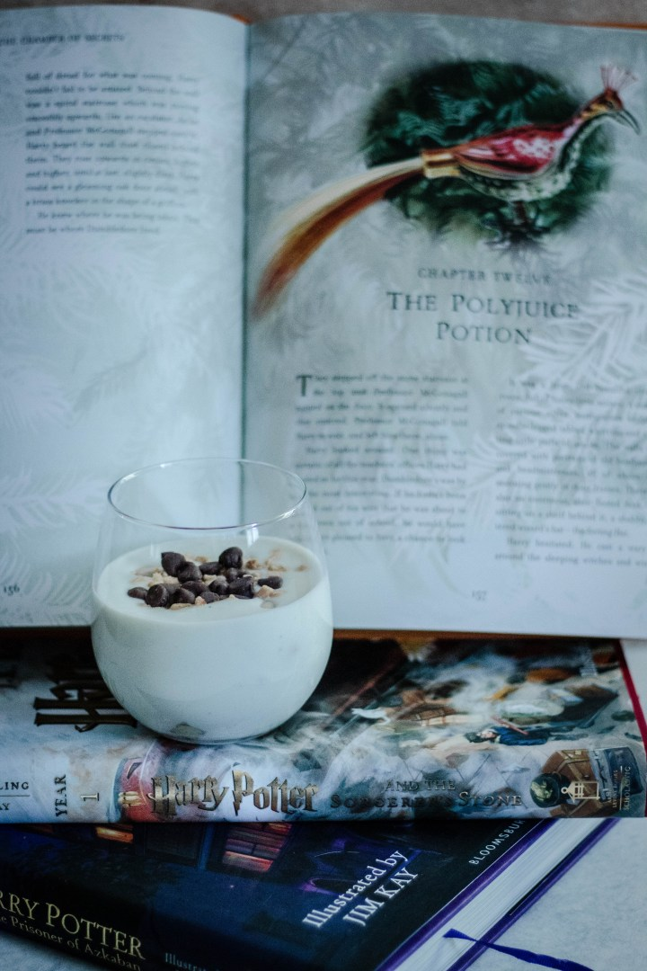 Polyjuice potion in a clear glass sitting in front of a book.