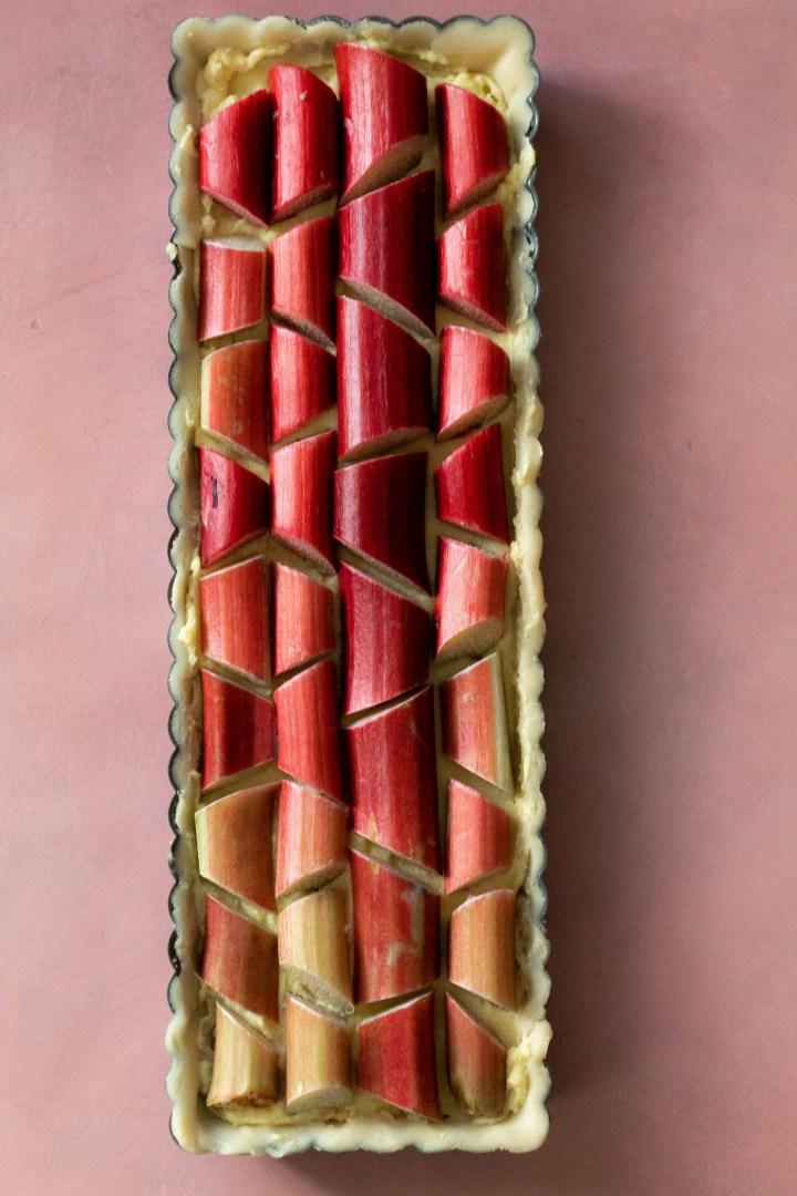 Rhubarb Tart Recipe on a pink background.