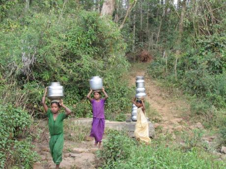 Girls and women collect water from a trickling spring in Vanabarangai