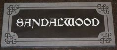 Slate house sign with raised Celtic border with letters painted white