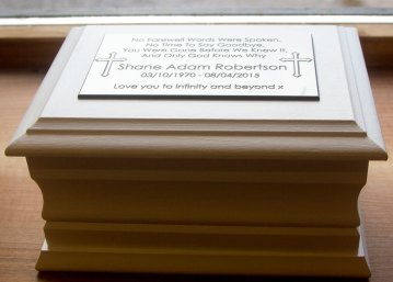 Casket with white engraved memorial plaque