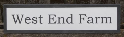 Slate house sign with raised letters and white background