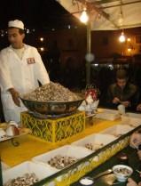 Cooking a giant pot of escargot in the markets of Marrakech, Morocco.