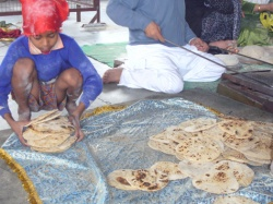 A small boy stacks Chapatis into a basket