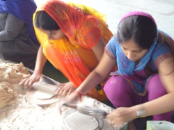 Young girls rolling chapatis from dough
