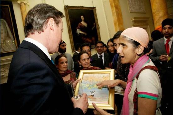Prime Minister David Cameron receiving oil painting of Sikh praying in Darbar Sahib sarovar from Mejindarpal Kaur, United Sikhs director