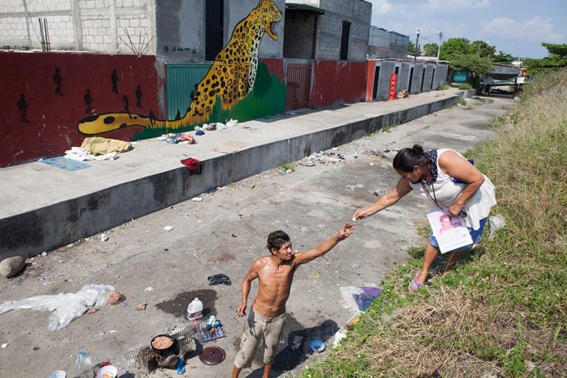 DICIEMBRE: Guadalupe JimŽnez, madre de Jose Daniel Mendoza Jimenez, entrega una moneda a un hombre que cocina a las orillas del rio Suchiate. (Prometeo Lucero)