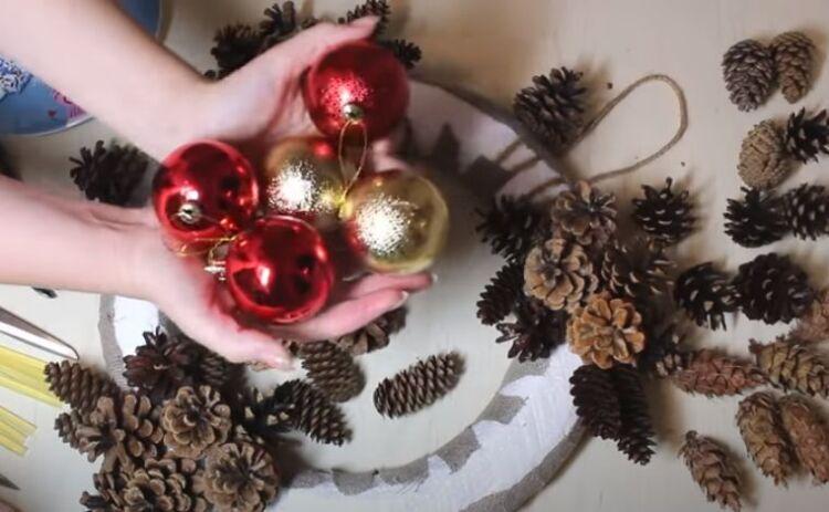 Corona di Natale sulla porta di coni e rami di abete