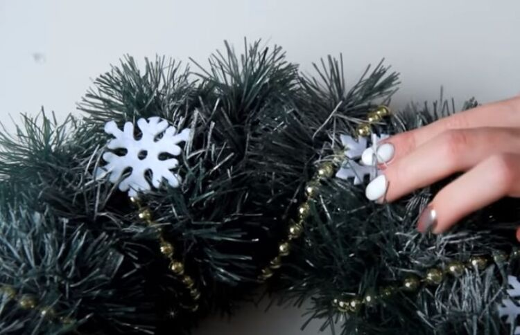Ghirlande del nuovo anno sulla porta con le loro mani dalla fidanzata e dalla tinella