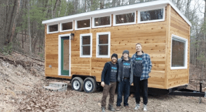 Three people stand in front of a tiny house in the woods.