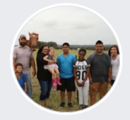 An image of a mixed race family with a horse in the background