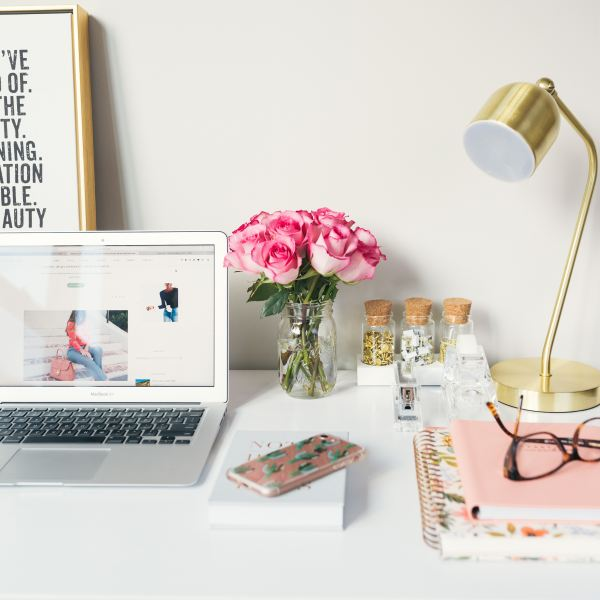 blogger subscription bundle image of laptop on desk surrounded by stationary with pink flowers in a vase next to a gold lamp