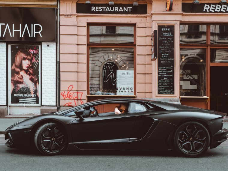 How Much Does Website Content Writing Cost feature image - Ferrari driving outside a restaurant