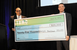A representative from Disease Diagnostic Group (right) accepting his $25,000 prize alongside Tulane professor Sherif Ebrahim (left) after the 2014 final round.