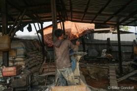 man operating stone grinder