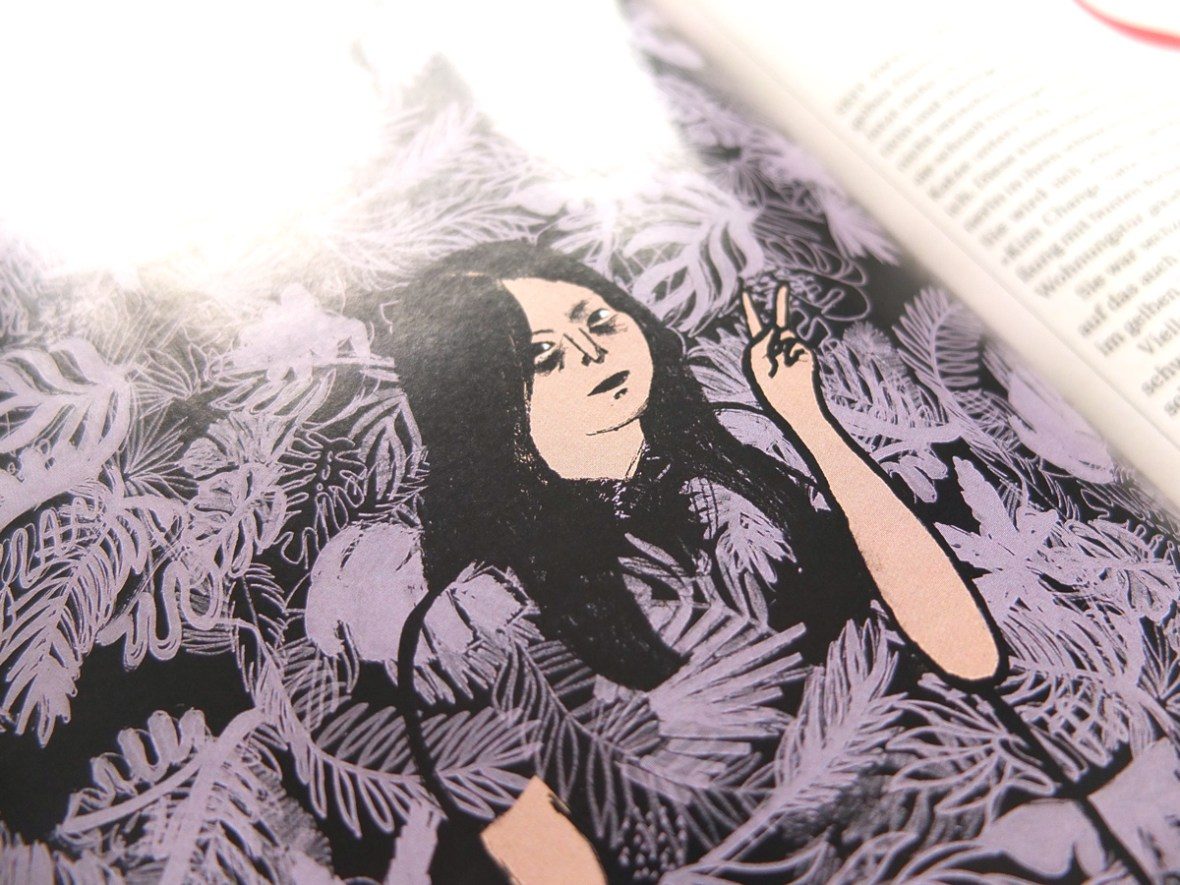 Vor eine schwarz-lila gemusterten Tapete mit großen Palmen und Zimmerpflanzen-Blättern steht ein südkoreanisches Mädchen und macht das Victory-Zeichen mit der rechten Hand, ihre Kleidung hat das Tapetenmuster und sie verschwindet fast im Hintergrund, Hanfblätter sind auch im muster, eine Katze ist darin auch versteckt. · Kim unterm Sofa · von Franziska Hauser, DAS MAGAZIN, Illustration: Silke Müller