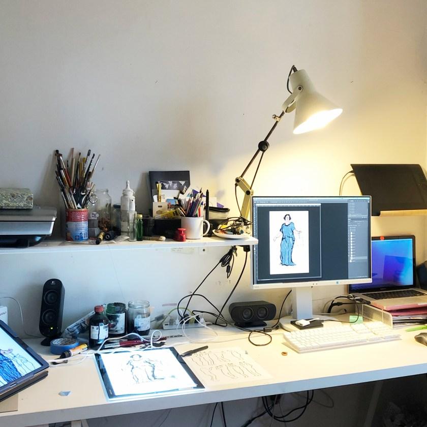 Foto vom Arbeitsplatz von Silke mit IPad, LEuchttisch zum Durchzeichnen, dem Monitor wo die Justitia Illustration sichtbar ist, Schreibtischlampe ist an.
