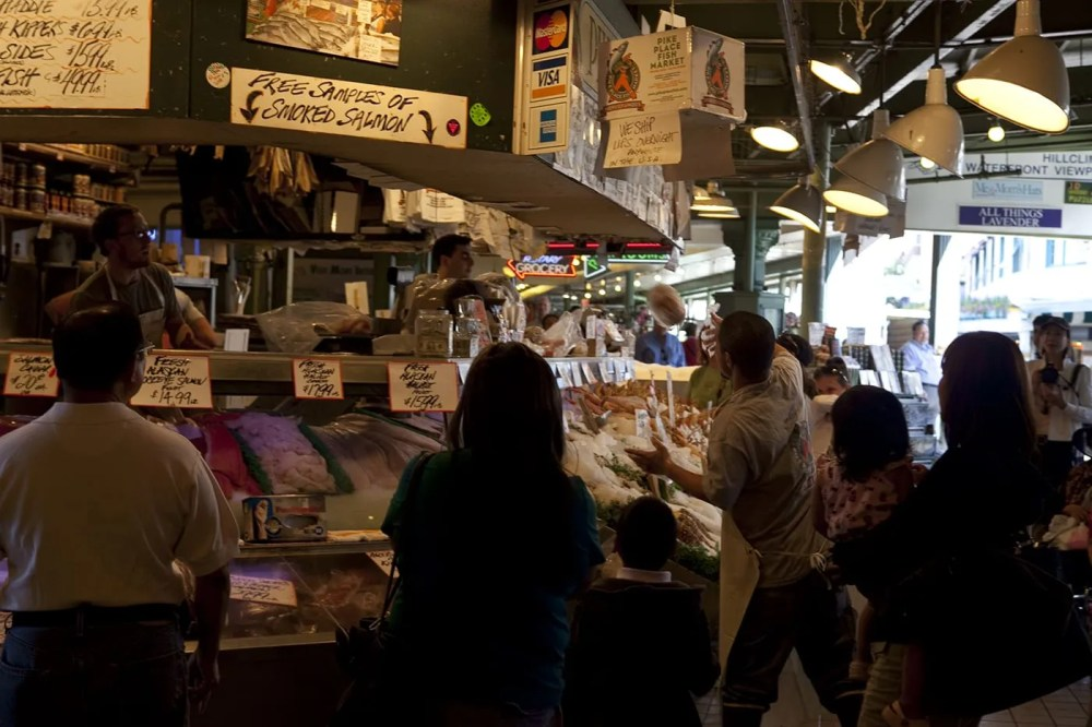 Fishmongers throwing fish at Pike Place Fish Market in Seattle, Washington.