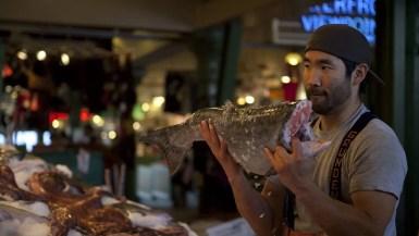 Fishmongers throwing fish at Pike Place Fish Market in Seattle, Washington.