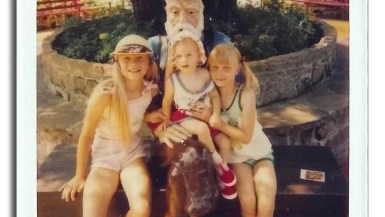 Val and her sisters with a statue of an old man