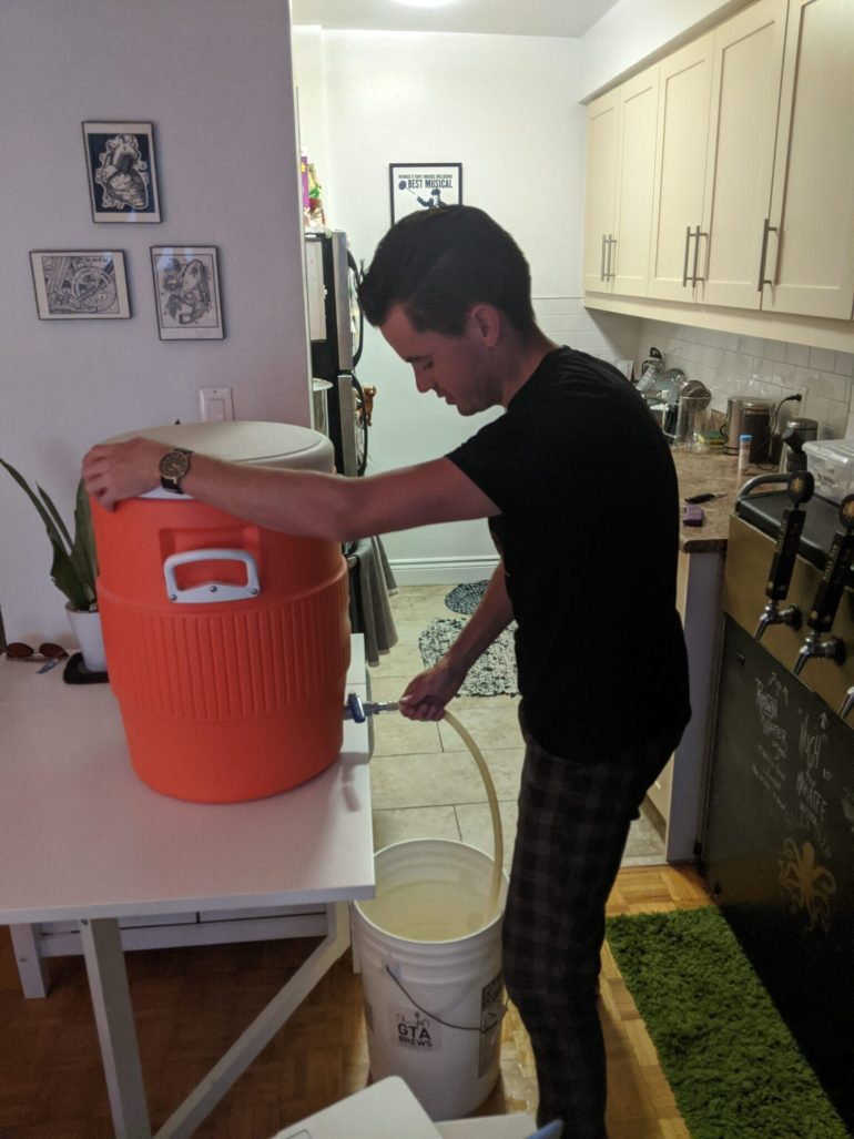 man brewing collects sparge runoff from cooler