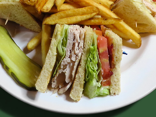 Close-up photo of turkey clubhouse sandwich served with a pickle and fries