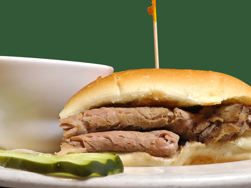 Photo of french dip sandwich served with container of au jus and a pickle slice