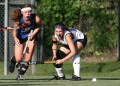 girls playing field hockey