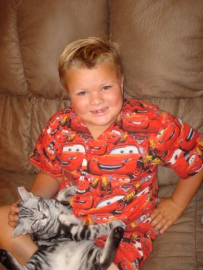 Image of Boy in pajamas sitting on sofa holding a sleeping silver tabby American Shorthair kitten