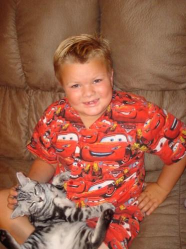 Image of Boy in pajamas sitting on sofa holding a sleeping silver tabby American Shorthair kitten