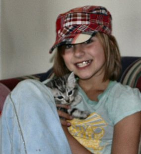 Image of girl wearing plaid hat holding American Shorthair silver tabby kitten