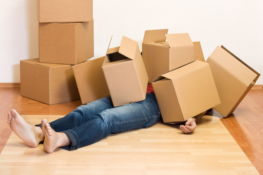 Overwhelmed homeowner under a pile of cardboard moving boxes.