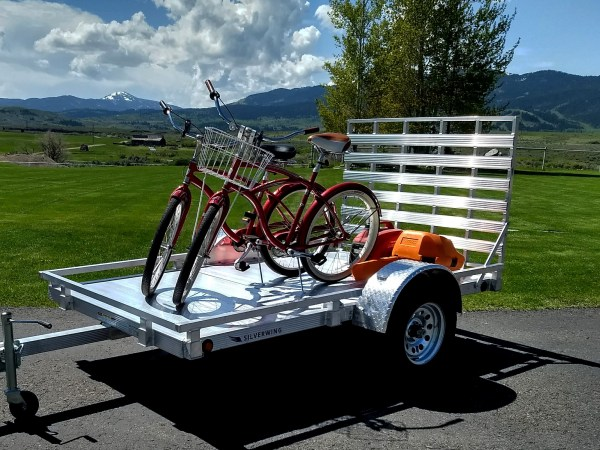 two regular bikes on the trailer with a chainsaw and gas can