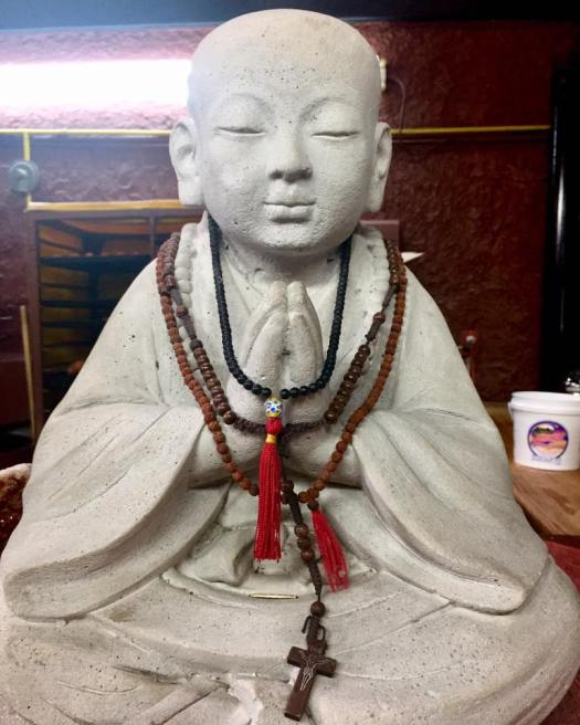 image of a buddha statue wearing a rosary