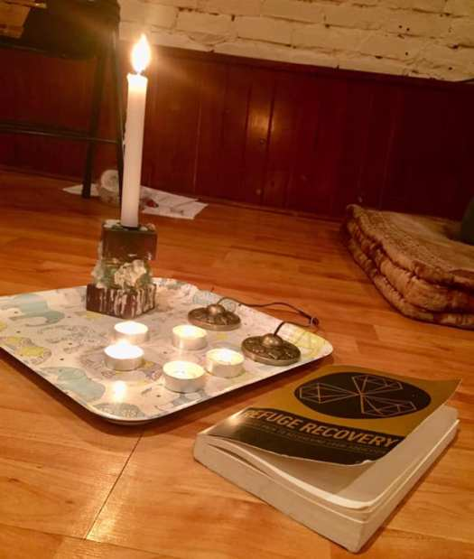 Several candles laid out ceremonially with meditation bells and a copy of the Refuge Recovery book